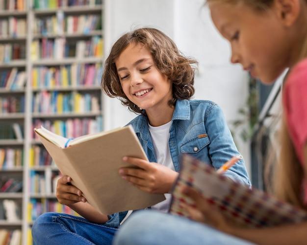 Niños leyendo y haciendo sus deberes.