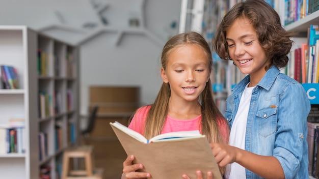 Niños leyendo un libro con espacio de copia.