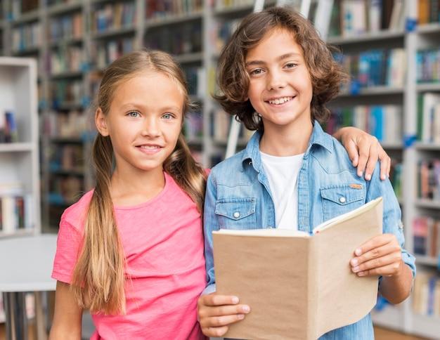 Niños leyendo un libro juntos en la biblioteca.