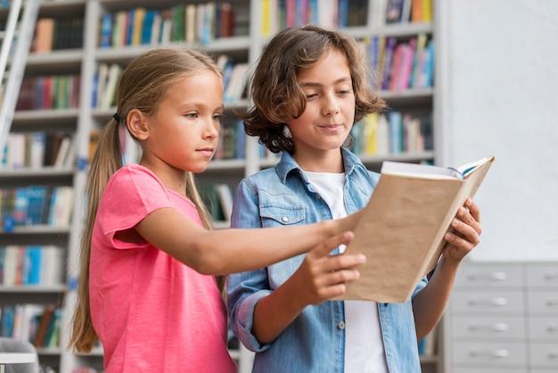 Niños leyendo un libro juntos.