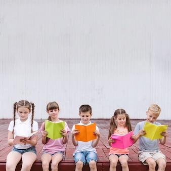 Niños leyendo libros con espacio de copia