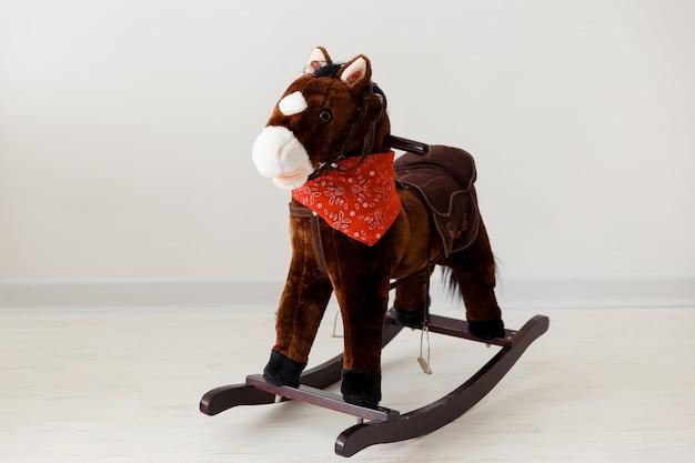 Los niños de la linda silla de caballo mecedora clásica vintage pueden disfrutar de la equitación en blanco.