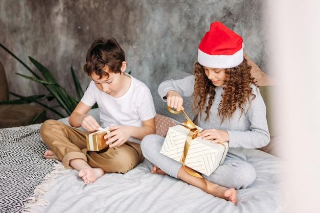 Niños lindos entre adolescentes con sombreros y pijamas de santa abren cajas de regalo de navidad en la cama con almohadas, tiempo de la mañana de navidad, fiesta infantil