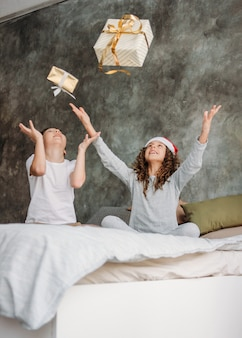 Niños lindos entre adolescentes con sombreros de santa y pijamas tiran cajas de regalo de navidad en la cama con almohada, tiempo de la mañana de navidad, fiesta para niños