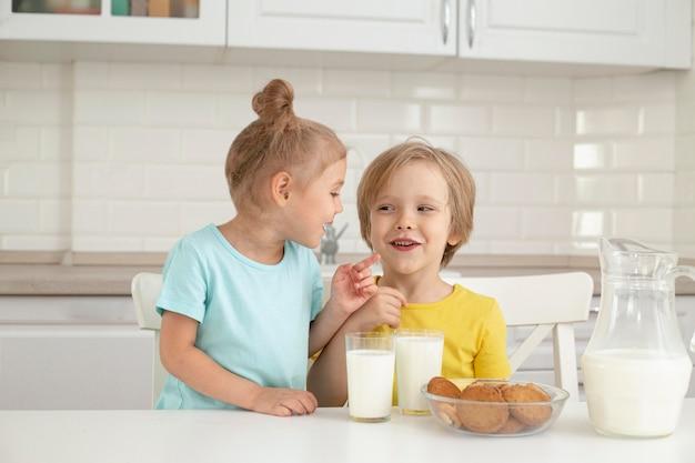 Niños lindos bebiendo leche en casa