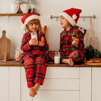 Niños lindos comiendo galletas de navidad y bebiendo leche