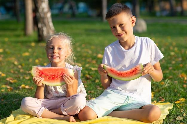Niños lindos comiendo sandía jugosa en el parque de otoño