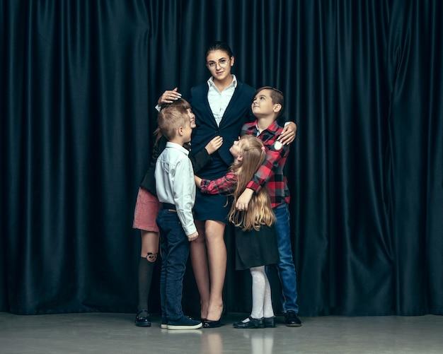 Niños lindos con estilo en estudio oscuro. las hermosas chicas adolescentes y el niño de pie juntos