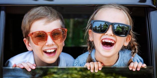 Niños lindos con grandes gafas de sol y grandes sonrisas.