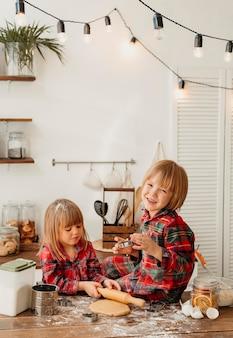 Niños lindos haciendo galletas de navidad juntos en la cocina