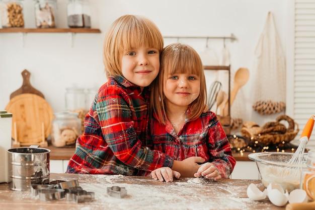 Niños lindos haciendo galletas de navidad juntos