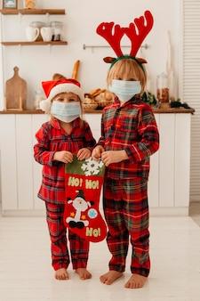Niños lindos con máscara médica sosteniendo un calcetín de navidad