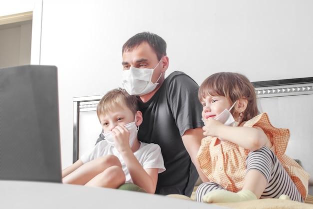 Niños lindos niño y niña y su padre en máscara médica está sentado en su casa en cuarentena.