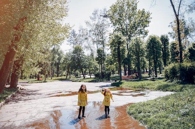 Niños lindos plaiyng en un día lluvioso