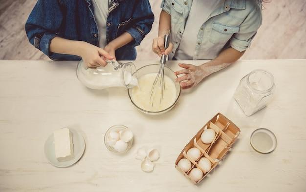 Niños lindos que preparan la masa mientras que cuecen en la cocina.