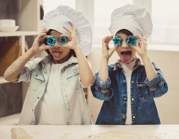 Niños lindos con sombreros de chef están jugando con galletas.