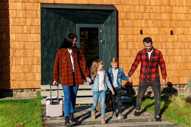 Niños lindos y sus padres felices saliendo de casa con maletas para vacaciones familiares.