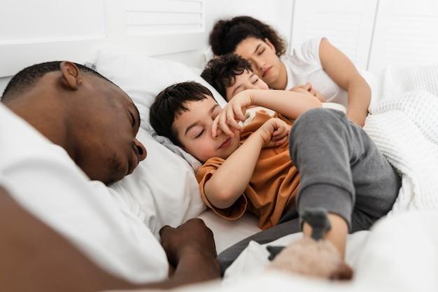 Niños lindos tratando de dormir en la cama de sus padres