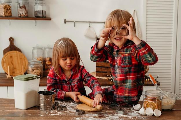 Niños lindos vista frontal haciendo galletas de navidad juntos