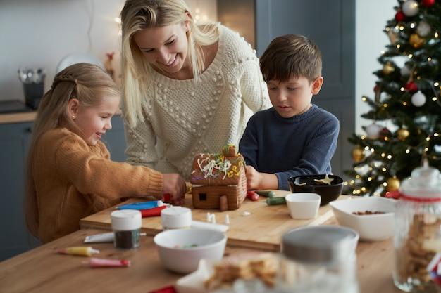 Los niños y la madre decorando la casa de pan de jengibre en la cocina