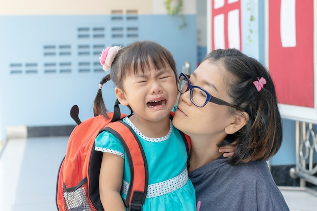 Los niños y la madre llorando el primer día van a la escuela de prejardín de infantes