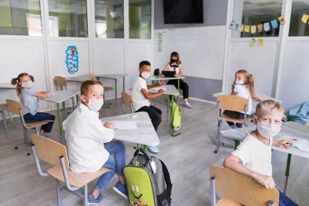 Niños y maestros con máscaras médicas durante la pandemia.