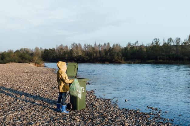 Los niños con las manos en los guantes recogiendo botellas vacías de plástico en una bolsa de basura cerca del lago