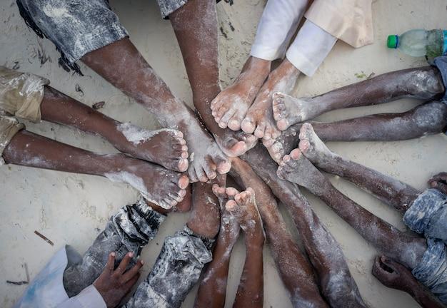 Niños manos y pies juntos en círculo