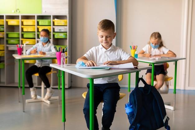 Niños manteniendo la distancia social en el aula.