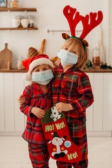 Niños con máscara médica sosteniendo un calcetín navideño