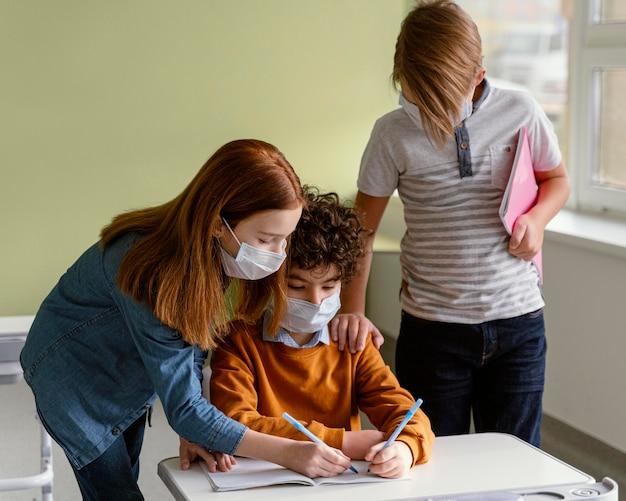 Niños con máscaras médicas aprendiendo en la escuela.