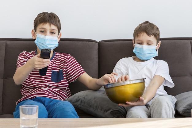 Niños con máscaras médicas mirando televisión y comiendo palomitas de maíz
