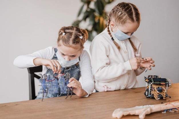 Niños con máscaras médicas que aprenden a usar componentes eléctricos.