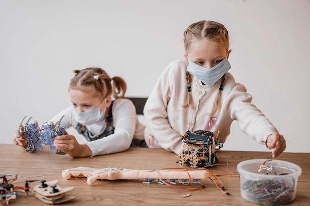 Niños con máscaras médicas que aprenden a utilizar componentes eléctricos.