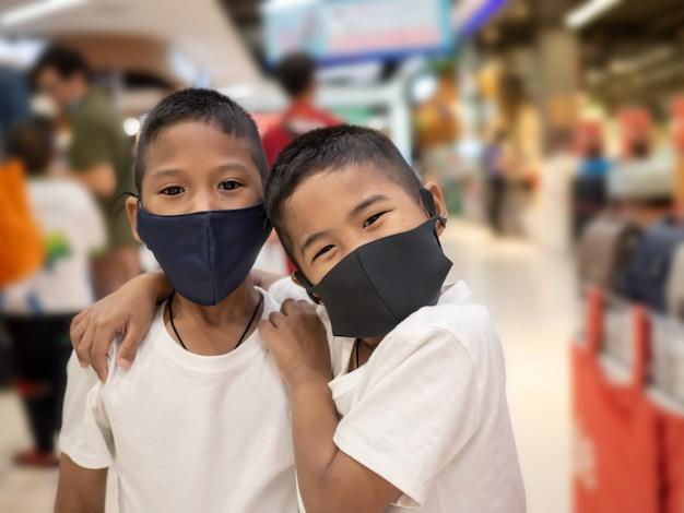 Niños con máscaras protectoras en el centro comercial.