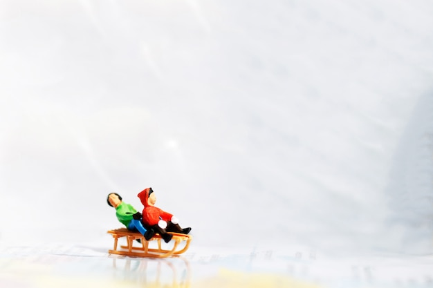 Niños en miniatura jugando diversión con deslizador de nieve.