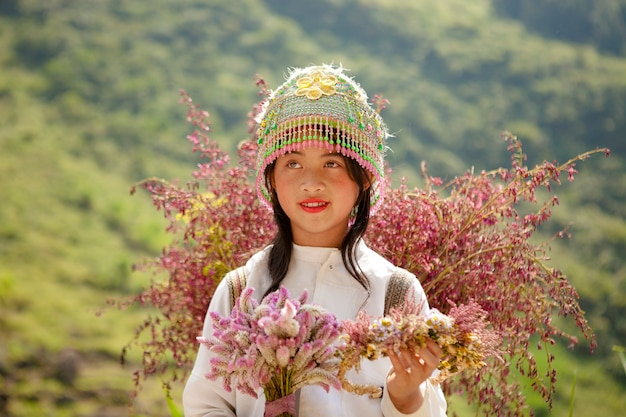 Niños de minorías étnicas no identificadas con cestas de flores de colza en hagiang, vietnam. hagiang es una provincia más al norte de vietnam