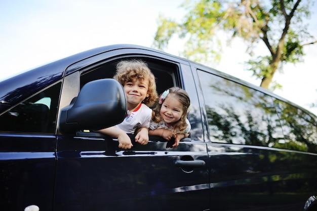 Los niños miran por la ventana de un carro.