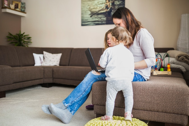 Niños mirando a su madre mirando portátil