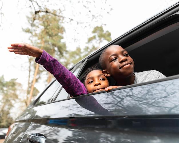 Niños mirando hacia afuera a través de la ventana de su auto