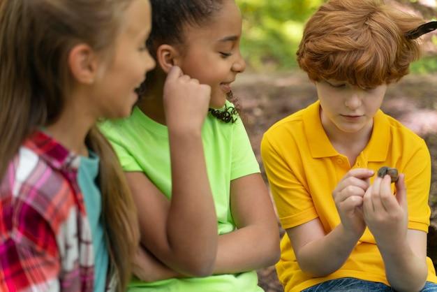 Niños mirando juntos un caracol.