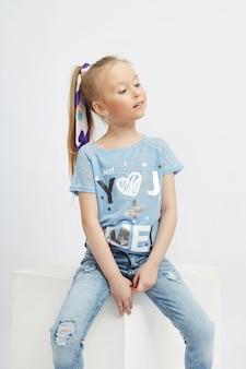 Los niños de moda posan para la ropa de mezclilla de primavera. alegría y diversión. pantalones