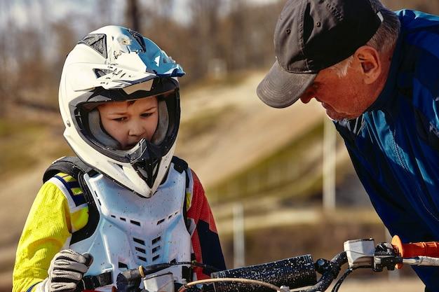 Niños montando en motobike, competencia junior en entrenador de motocicleta da instrucciones a su joven piloto.