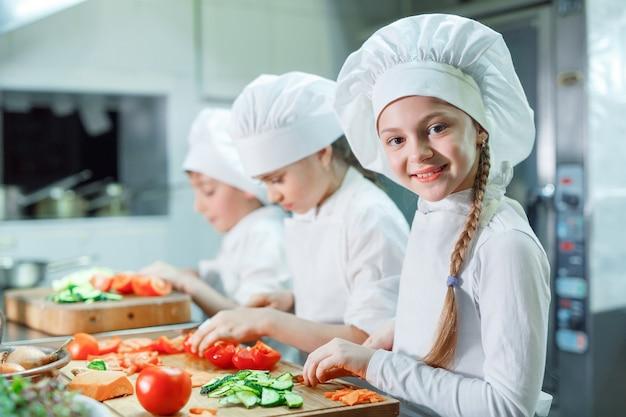 Los niños muelen las verduras en la cocina.