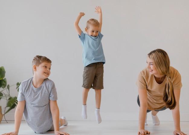 Niños y mujer sonriente de tiro completo