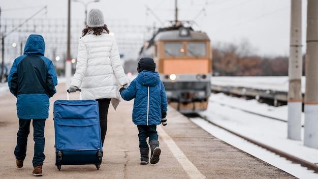 Niños y mujer de tiro completo en la estación de tren