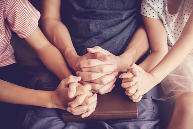 Niños multiculturales rezando con su padre en casa.