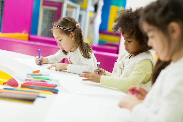 Niños multirraciales dibujando en la sala de juegos.