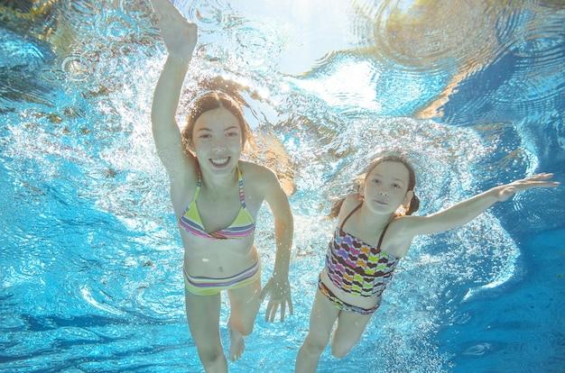Los niños nadan bajo el agua en la piscina, las niñas activas y felices se divierten bajo el agua, los niños hacen ejercicio y practican deporte en vacaciones familiares activas
