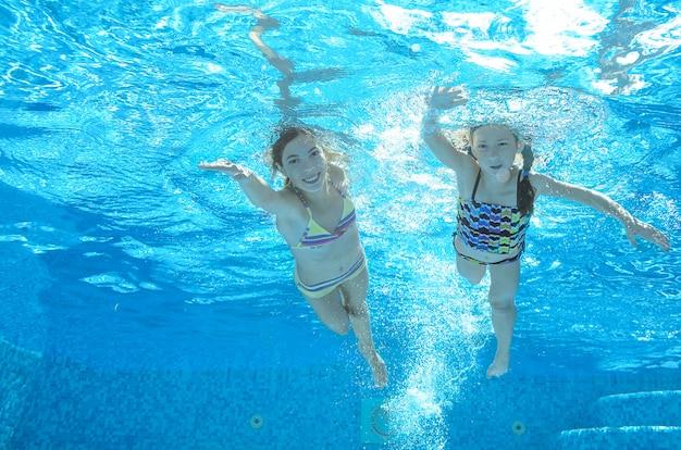 Los niños nadan bajo el agua en la piscina, las niñas activas y felices se divierten bajo el agua